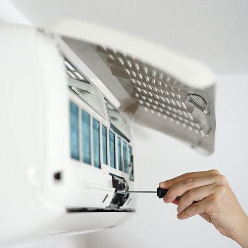 A Technician Adjusts a Mini-Split AC.