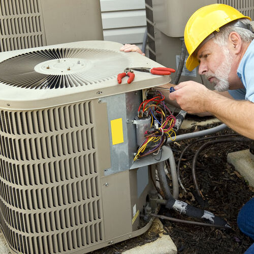 An HVAC Technician Repairs an Air Conditioner.
