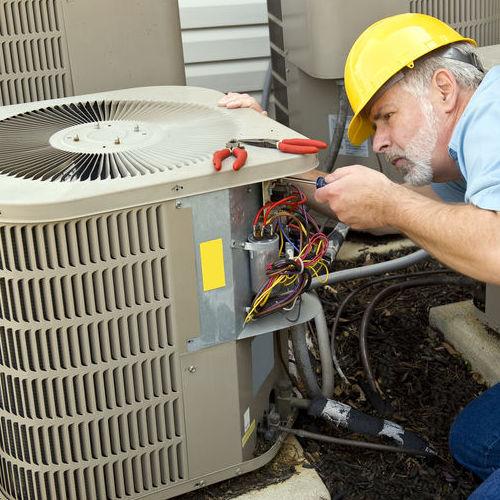 a Technician Repairs an Air Conditioner.